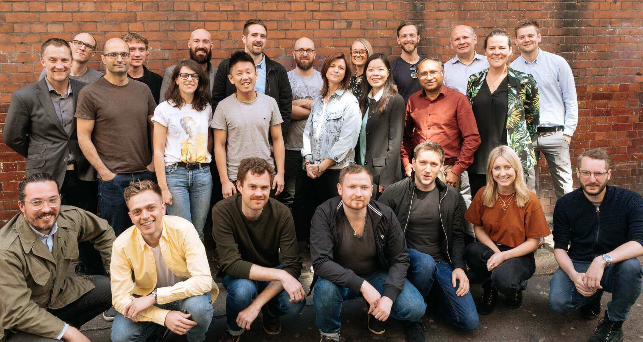 Group photo of the buzzvault team showing 24 people in front of an orange brick wall